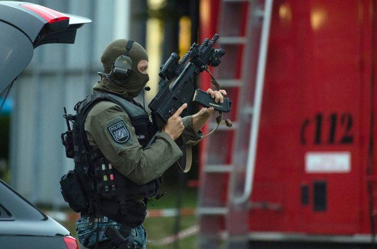 Un francotirador de las fuerzas especiales, coloca el cargador de su arma reglamentaria y toma posiciones en el entorno del centro comercial.