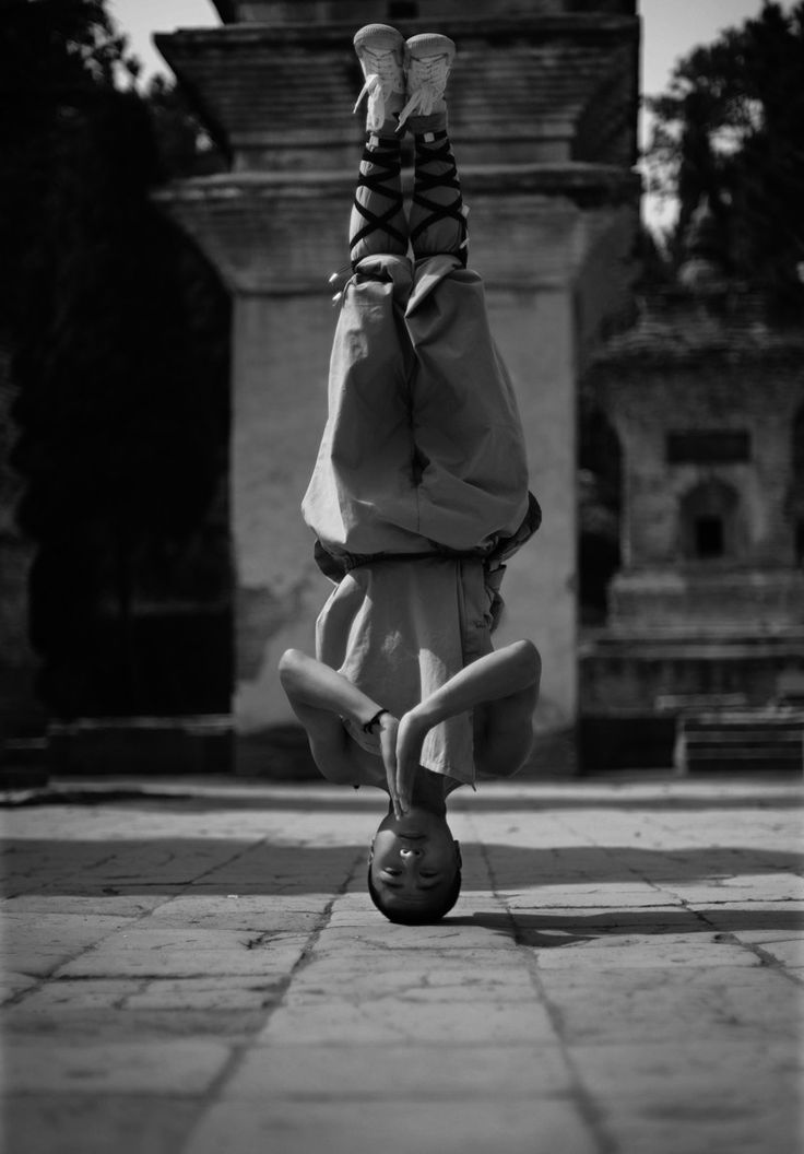 world martial arts Shaolin Monk doing headstand Black and white photo