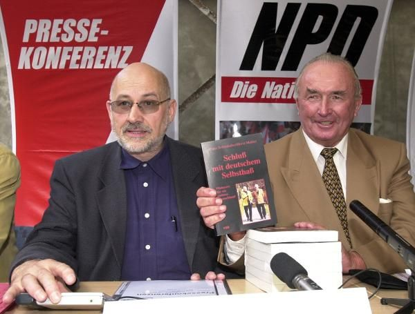 """Franz Schönhuber (1923-2005) (right) and Horst Mahler (left) introduce their book Schluss mit deutschem Selbsthass [No More German Self-Hatred] at a press conference organized by the National Democratic Party of Germany [Nationaldemokratische Partei Deutschland or NDP] in Berlin on September 7, 2000. A former member of the Waffen-SS, Schönhuber worked as a journalist after the war but was eventually fired because of his radical views. He founded the extreme right-wing party """"Die…"""