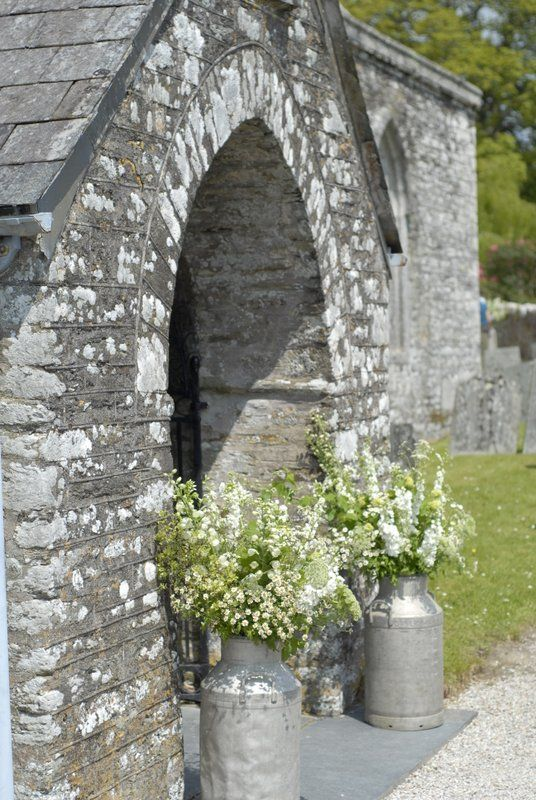 milk churns with white flowers