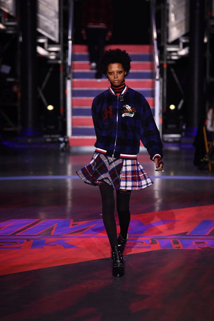 Londone Myers walks with purpose in the Hilfiger Collection Tartan Fleece Bomber Jacket and Hilfiger Collection Wool Blend Pleated Tartan Skirt.