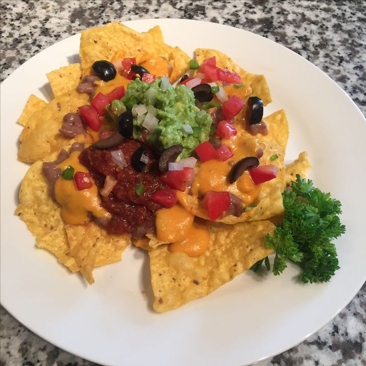 #nachos with #tostitos #cantina #chips #refried #beans #nocheese #cheesesauce made out #potatoes #carrots and #nutritional #yeast, #chopped #jalapeños #onions #tomatoes #blackolives #guacamole and #homemade #salsa #yummy #foodie #sprouts #winco #kroger #centralmarket #traderjoes