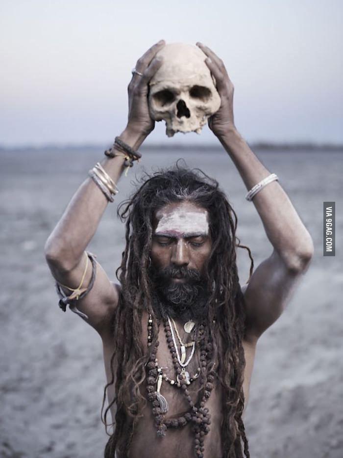 A Sadhu holding a skull in his hand and praying the god - Varanasi, India