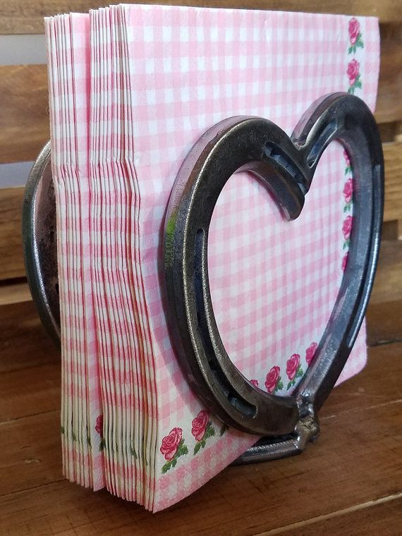 Feel the love!! No kitchen has enough love in it till you've added this lovely napkin holder to your counter or dining table. Made with genuine horseshoe and consisting of 2 large hearts with a small heart for the base. If you love hearts this delightful horseshoe piece makes a great addition to your farmhouse country kitchen. Get it in natural, as seen in the photo, or get it in one of the color options. Because each item is handmade and made to order no 2 are ever exactly alike. =&#x3...