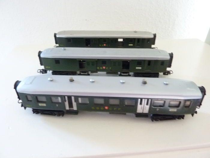 Märklin H0 - 348/4015/-17 - Passagiersrijtuig en 2x Bagagerijtuig van de SBB met beweegbare deuren via draaiknoppen op het dak  Deze 3 rijtuigen van de SBB / CFF van de Zwitserse Spoorwegen stamt uit de midjaren 50/60. Zijn in goede maar gebruikte staat zonder verpakking. Ze hebben wat gebruikssporen. Ze zijn vierassig donkergroen met grijs dak. Lengte over de buffers is 21 cm. Opschrift : 1 x 348/1 en 2 x 4017. Draaistel is van metaal met aan buitenkant kunststof. Rest is geheel van metaal…