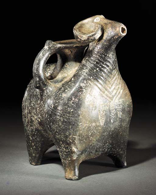 AN URARTIAN BLACK BURNISHED POTTERY RAM RHYTON  9TH-8TH CENTURY B.C.  The animal…