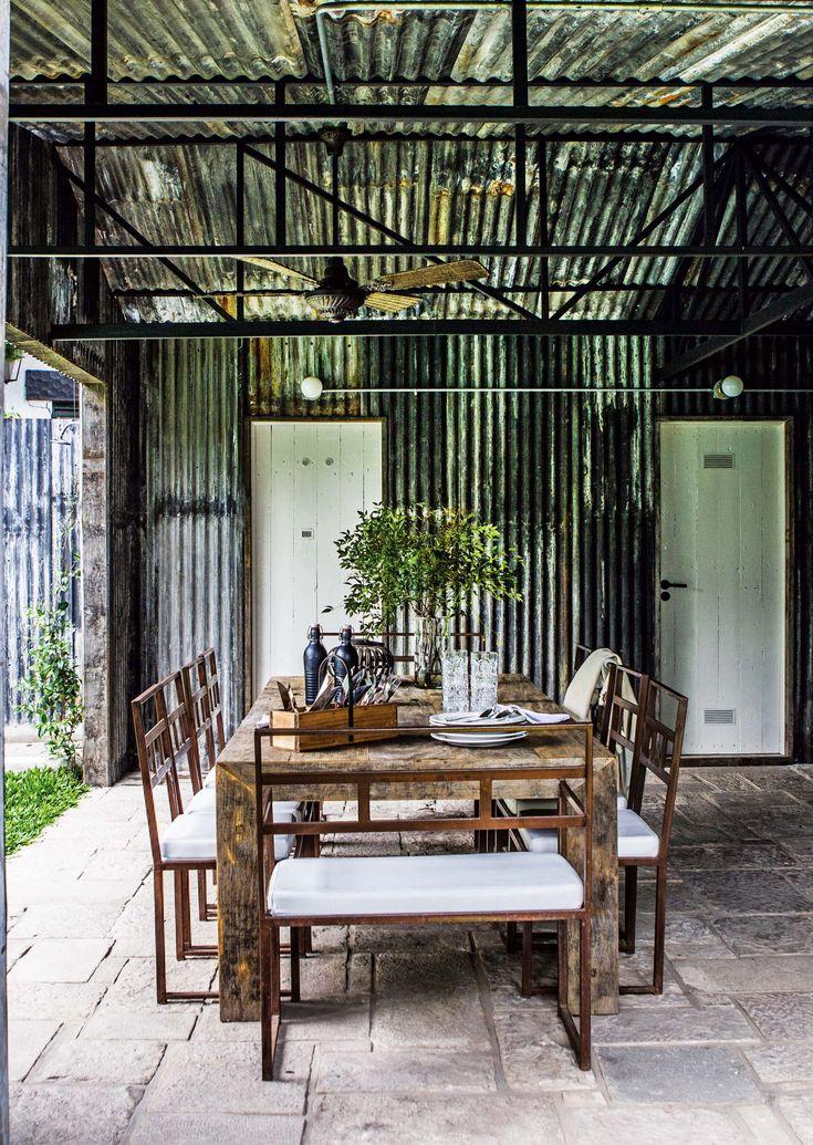 Quincho rústico en el jardín de una casa con gran mesa hecha con tablones de lapacho gris (Pablo Ledesma) y combinada con sillas de hierro. Arriba, ventilador de techo.