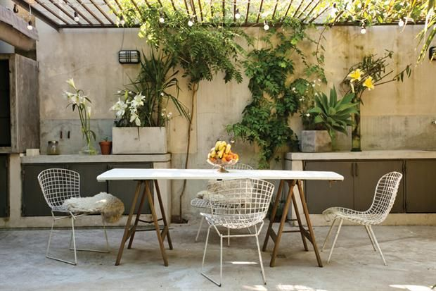 En el comedor al aire libre, una sencilla mesa con caballetes rodeada por sillas Bertoia ($1.512, Newton). Macetas (Puerto de frutos de Tigre)..  Foto:Living /Daniel Karp