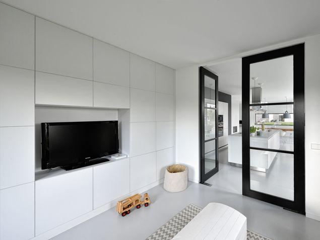 Strakke witte televisiekast in kinderkamer. De speelkamer krijgt een fris en licht karakter door de witte wandkast, de lichtgrijze gietvloer en zwarte deuren. Ontwerp BNLA architecten | Fotografie Studio de Nooyer