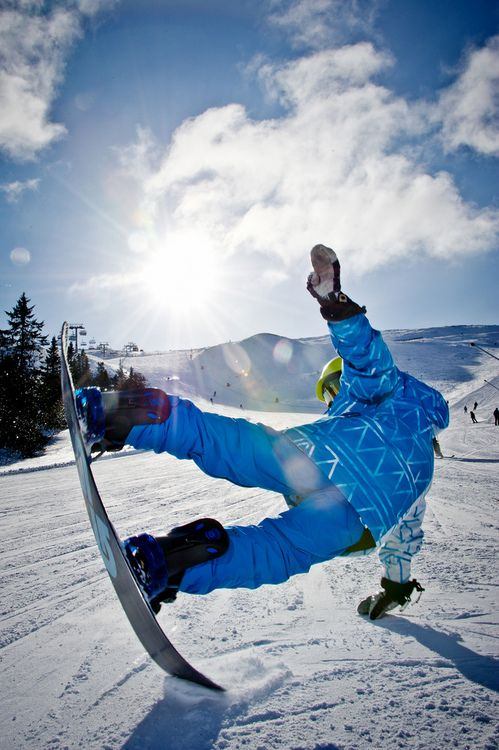 Snowboarding - a winter sport and the act of riding on and performing tricks with a snowboard on slope.