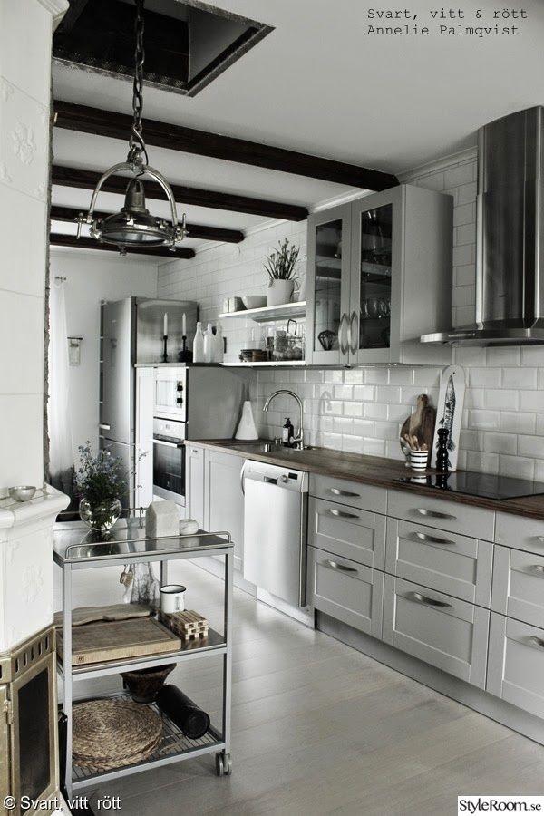 serveringsvagn,industristil,industriellt kök,vitrinskåp kök,gråa köksluckor,vitt kakel upp till taket,takbalkar,industrilampa,bänkskiva,fläkt,kylskåp,rostfritt i köket,kök