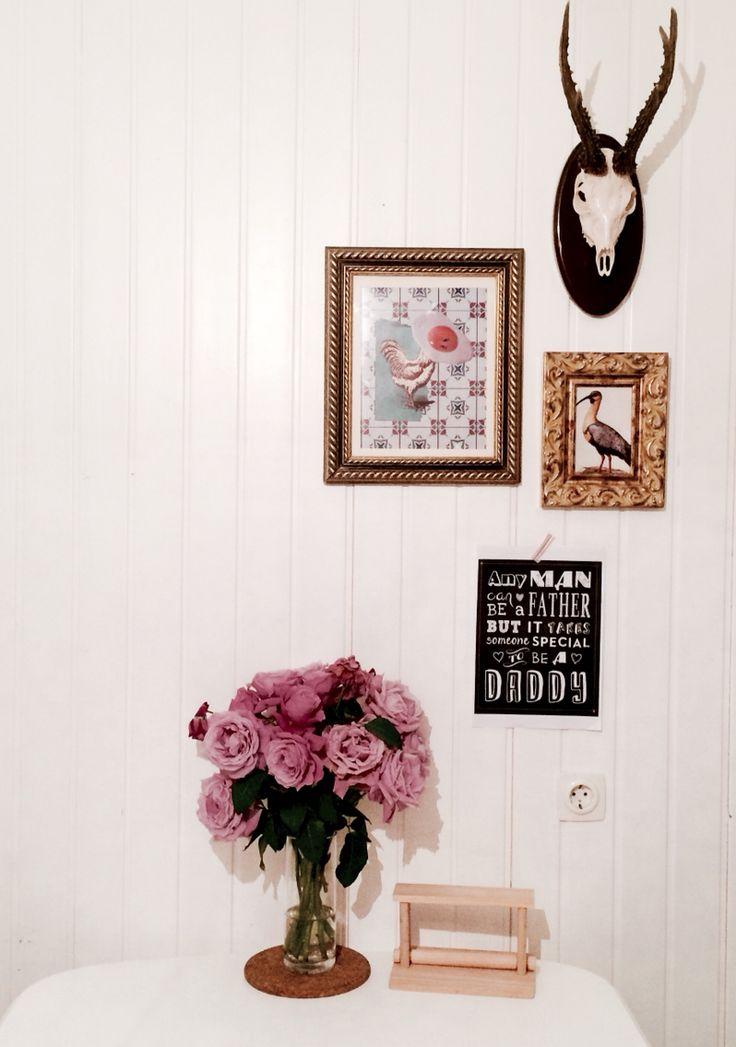 Una pared de la cocina. Ilustraciones, cuadro de pájaro y cornamenta de corzo... Sobre pared de madera blanca