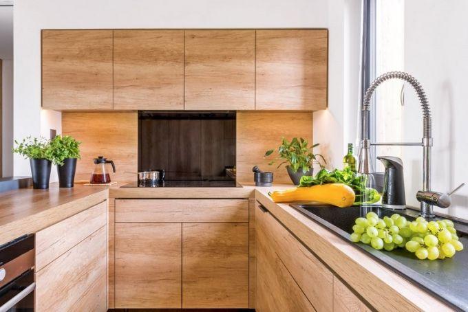 Kompaktní kuchyň je zhotovená podle autorského návrhu majitele v dekoru dubu, který příjemně kontrastuje s granitovým dřezem Blanco. Je praktická, vše je pěkně po ruce a nikam není daleko. Kuchyň je vybavena všemi základními vestavnými spotřebiči Bauknecht. Nechybí ani skříňka, v níž se ukrývá automatický kapslový kávovar
