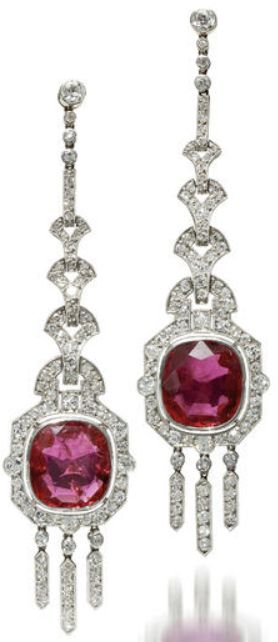 A pair of art deco ruby and diamond pendant earrings, Mauboussin, 1924,  each designed as an oval-shaped ruby within an old European-cut diamond surround suspended from a geometric line of old European-cut diamonds; with maker's mark, no. 81513; rubies each weighing approximately: 4.45 carats; mounted in platinum; length: 2 3/4in. Via Bonhams.