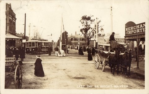 Last day of busses, Malvern, ca. 1910. The postcard is taken looking east corner from the corner of Glenferrie Road and Wattletree Road, Malvern. Moran and Cato, Merchants and Importers store is located on the right. The tram is turning the corner down Wattletree Road and the horse drawn bus is pulled up at the corner.