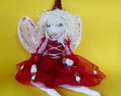"Fairy ""Magic"" will listen for endless hours and will never judge as you are always right.  She can help out by sprinkling a little fairy dust, pink dust is her favorite.  She is just beautiful with her organza dress dotted with flowers and hand embroidered hat. I hope you can see the detail. The body is made from embroidered satin, and she sits demurely on any shelf of table. Her wings are organza. Aprox 14cm high.   SOLD"