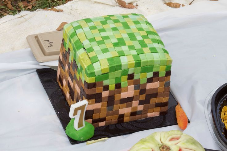 "Hadar's 7th Minecraft Birthday cake This cake took so so long to make. I thought 'how simple would a grass block be!' How wrong I was. It took at least 4 hours to cut all the blocks. Then at least 6 to place them!! My son's reaction... ""oh a grass block"" I think a energy block would have been more loved."