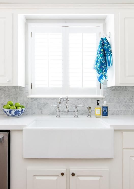 A window covered in a white shutters is flanked by off-white cabinets accented with nickel hex knobs and positioned above a farmhouse sink with a polished nickel vintage deck mount faucet.