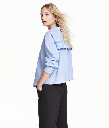 Wide-cut, long-sleeved blouse in cotton poplin with decorative ruffle trim at back. Chest pocket, buttons at front, and gently rounded hem.