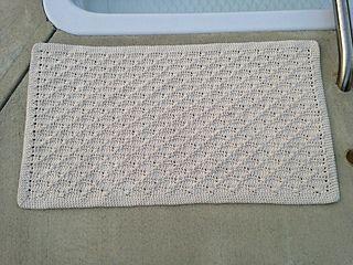 A crocheted cotton bathmat.