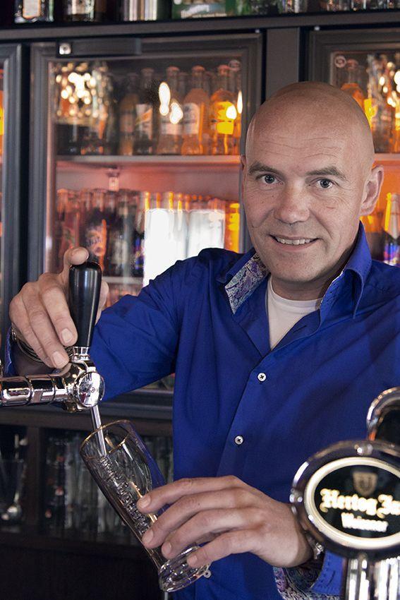 Portret van Jeroen, achter de tap van zijn grand café.