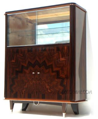 French Art Deco / Art Moderne Vitrine or Bar Cabinet, Circa 1940s    Spectacular French Moderne Cabinet with elaborate sunburst marquetry work.    Exotic macassar ebony veneers were expertly patterned to form a geometric sunburst pattern on the two lower doors, with upper by pass glass cabinet that has a mirrored back and sycamore interior.