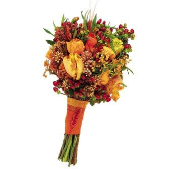 Hypericum berries sprout from this bouquet of apricot parrot tulips, orange ranunculus, orange asclepias, and seeded eucalyptus. Michelle Rago See fall wedding centerpiece ideas here.