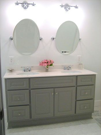 Wow ... sage-y grey is very appealing. Looks timeless and modern. Also like the round mirrors and the symmetry of the space.