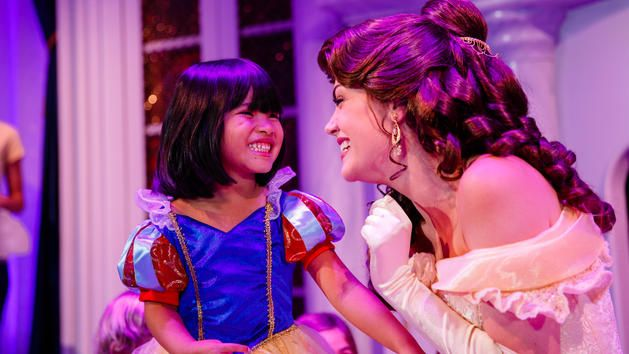 A little girl dressed as Snow White smiles as she meets Belle at Enchanted Tales with Belle