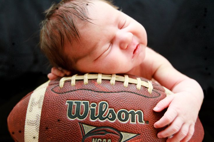 Newborn Boy Photos  -Football props are a way to keep things manly.. Using good ole' Dad's own football is a way to keep it personal! newborn boy photo ideas, newborn boy football  photo, newborn photo with football, football themed nursery