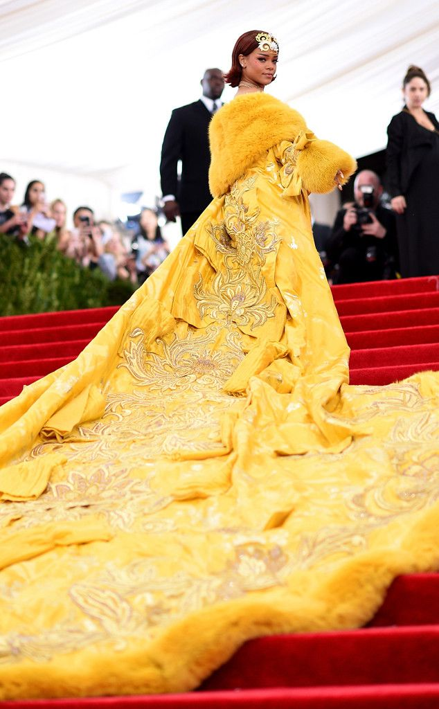 2015 Met Gala: Rihanna is wearing a long gold cape with embellishments and fur lining by Chinese designer Guo Pei. Spot on with the theme, Rihanna! One of the most talked about dress at the Met Gala! Only Rihanna can pull this exquisite cape off!
