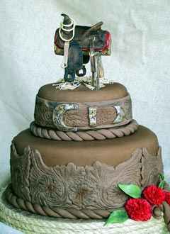 Brown two tier western style wedding cake decorate with intricate western designs and saddle wedding cake topper and garnished with red carnations. From www.paulascakecreations.com         ........   #wedding #cake #birthday