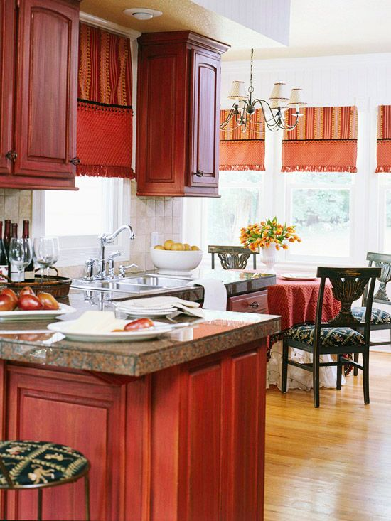 "Wow, these are painted cabinets? ""Two layers of paint transform plain wood cabinets: a red latex base coat coupled with a top coat of oil-base paint (black and raw umber) mixed with oil-base glazing liquid and paint thinner. Basket-style metal hardware suits the decorative paint finish."""