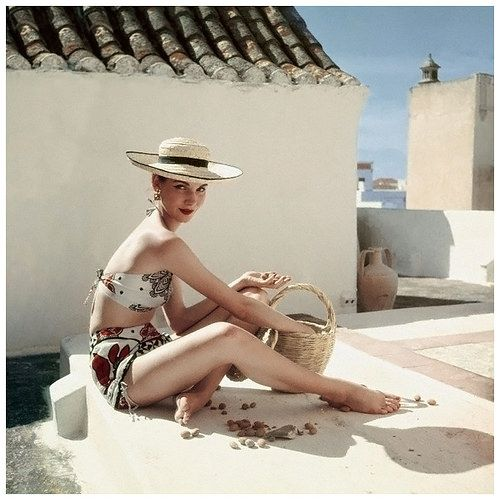 Model Cherry Nelms seated with basket on a rooftop, wearing Calypso designed patterned bikini. Circa June 1952 Olhao, Portugal Photo Henry Clarke