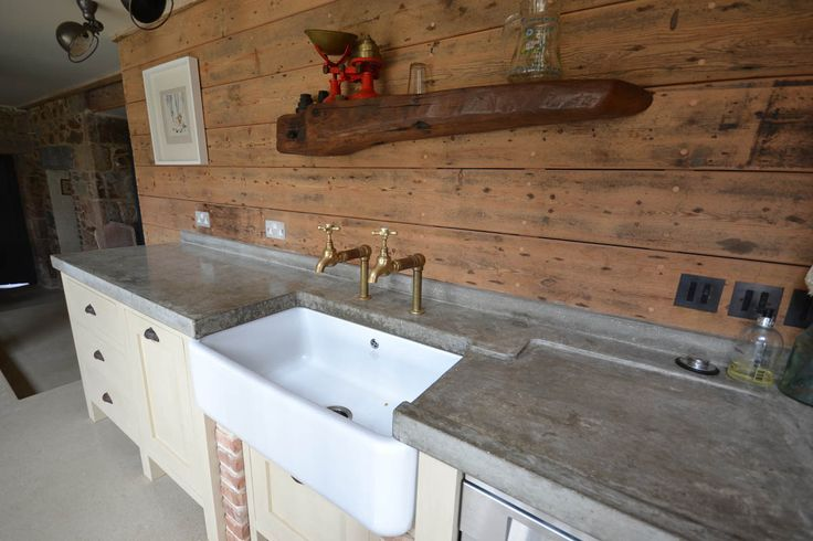 aPolished concrete worktop worktops countertops rustic bib taps large butler sink belfast reclaimed timber wall panels panelling weathered vintage cup handles sloped drainer eclectic kitchen interior
