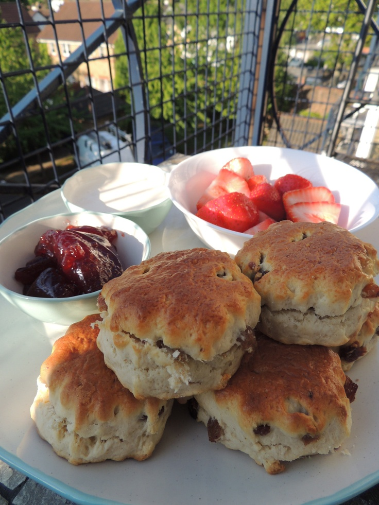 Scones topped with fresh strawberries, jam and cream