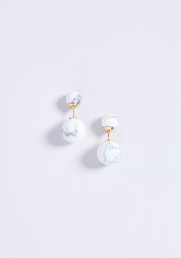 <p>A fresh take on Amber Sceats' classic pearl studs, the Ellipse Studs feature two white marble spheres and 18k gold plated stainless steel contrast.</p>
