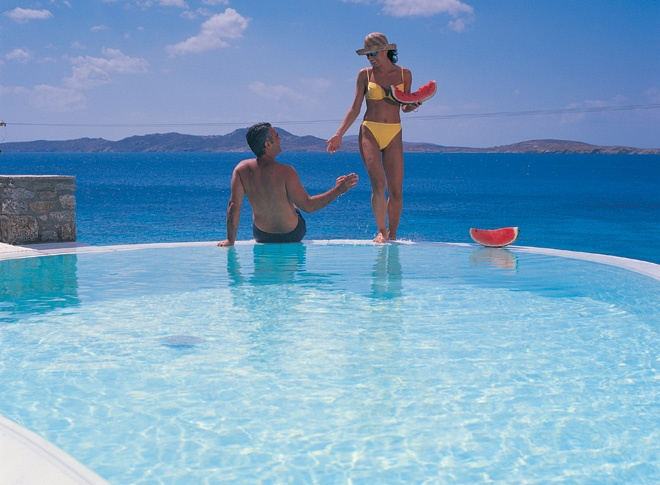 A couple enjoying their summer vacation in a Mykonos Grand Suite Private Pool with a view of the Aegean sea.