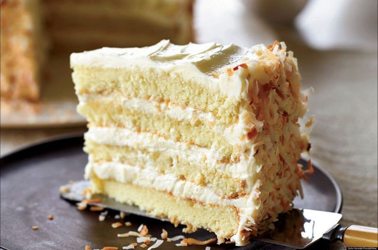 """A delicious coconut cake made from a cake mix with coconut cream cheese frosting and garnished with toasted coconut."""