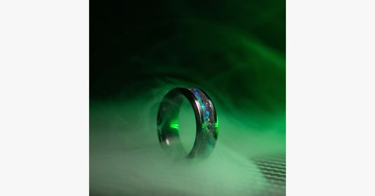 Description: Prepare to storm on Area 51 with this alien-themed glow-stone ring. The Area 51 Alien Ring incorporates a black ceramic base and features Alien Bloodstone opal, Nuclear Green opal, and meteorite shavings. These extraterrestrial inlay materials are complimented with black and purple glow-stone pigments. The ring glows bright colors at night, which will prove extremely useful when raiding Area 51. Highlights: Item Type: Rings Fine or Fashion: Fashion Gender: Women/Men Style: Classic M