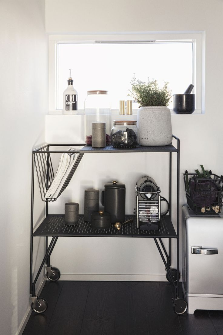 A trolley is used to store a beautiful mix of kitchen supplies and magazines. The sleek design and black metal add a stylish twist to the décor while providing flexible storage and extra work space for food preparation.