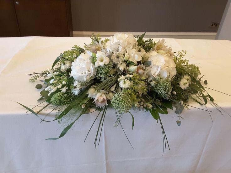 Registrar table arrangement of white flowers including Hydrangeas and Bouvardia