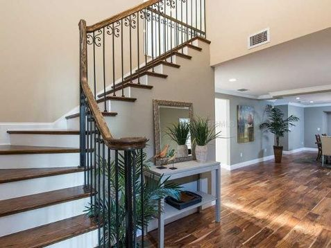As soon as you enter the mansion, you'll notice an open floor plan with Acacia wood flooring and iron railings along the stair case. = Beautiful floor