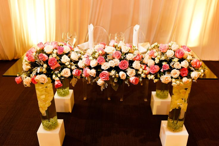 Gorgeous modern sweetheart table with luxe floral garland, ghost chairs and floating flower vases as table legs. Amazing! | Destination Wedding at Barcelo Maya Palace | Mexico wedding venues (FineArt Studio Photography)