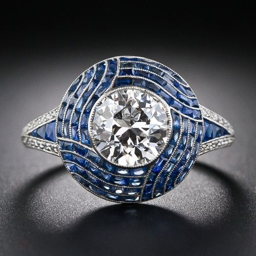 The 1.99 carat European-cut center stone sparkles mightily from atop a platinum dome, intricately adorned with mosaic-like, scissor-cut sapphires artfully arranged in an hypnotic, four-row swirl pattern. 'V' shape diamond and calibre sapphire shoulders decoratively support the top and a graceful openwork gallery adds a finishing flourish. A radiant and remarkable  Art Deco treasure.