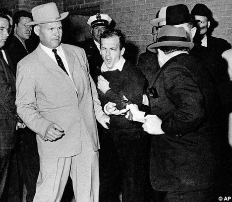 JFK's assassin Lee Harvey Oswald at the moment he was fatally shot by Jack Ruby in the basement car park at the Dallas Police Dept