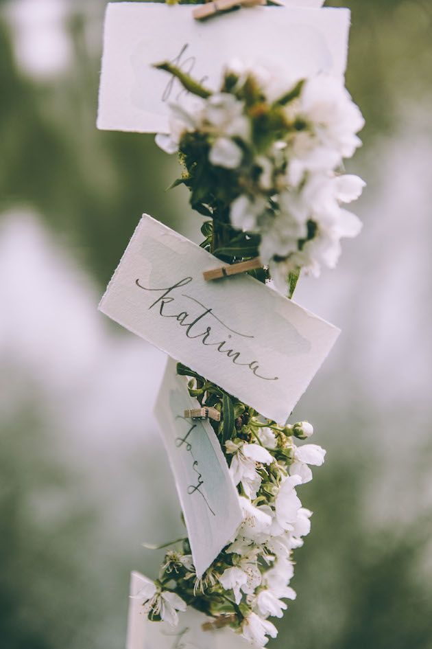 watercolour escort cards on floral arch