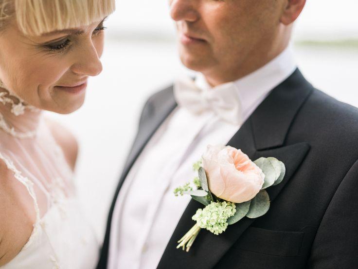 Brudgummens corsage med pion, daggkåpa och eukalyptus på vänster kavajslag, som klassiskt matchar brudens bukett.