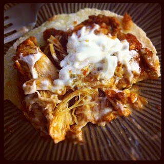 Slow cooker chicken with cilantro, lime, salsa, taco seasoning. Served on a corn tortilla with sour cream