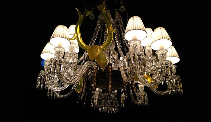 One of Philippe Starck's chandeliers for Baccarat, featuring three yellow glass deer heads with antlers.